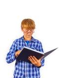 El muchacho elegante que desgasta los vidrios está leyendo en un libro Imagenes de archivo