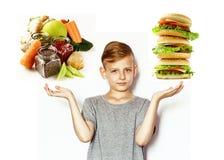 El muchacho elige entre la comida sana y los alimentos de preparación rápida Foto de archivo