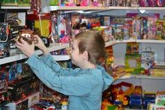 El muchacho elige un juguete en tienda de juguete Fotografía de archivo