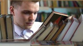 El muchacho elige un libro en la biblioteca Cierre para arriba metrajes