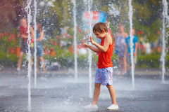 El muchacho emocionado que se divierte entre el agua salpica, en fuente Verano en la ciudad Foto de archivo