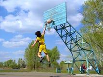 El muchacho en amarillo juega a baloncesto imagen de archivo