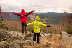 El muchacho en amarillo y el hombre en chaqueta caliente roja se colocan en una roca en un día de primavera ventoso frío Forma de Imágenes de archivo libres de regalías