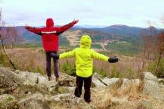 El muchacho en amarillo y el hombre en chaqueta caliente roja se colocan en una roca en un día de primavera ventoso frío Forma de Fotografía de archivo