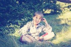 El muchacho en auriculares se sienta y medita en la hierba enorme Imagenes de archivo