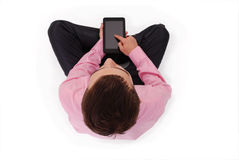 El muchacho en camisa rosada sienta y sostiene la tableta Imagenes de archivo