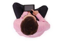 El muchacho en camisa rosada sienta y sostiene la tableta Fotografía de archivo