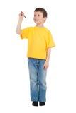 El muchacho en camiseta amarilla escribe Fotografía de archivo libre de regalías