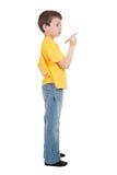 El muchacho en camiseta amarilla escribe Imagenes de archivo