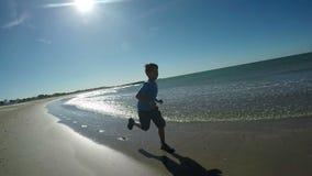 El muchacho en camiseta azul corre a lo largo de la playa almacen de metraje de vídeo