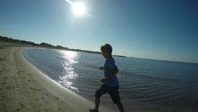 El muchacho en camiseta azul corre a lo largo de la playa metrajes