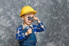 El muchacho en el casco amarillo que sostiene una llave de tubo en las manos fotografía de archivo