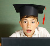 El muchacho en casquillo de la graduación consigue conocimiento de Internet fotos de archivo libres de regalías