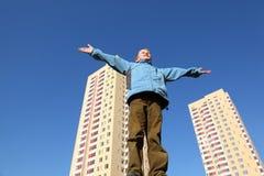 El muchacho en chaqueta levanta sus brazos al cielo azul Imágenes de archivo libres de regalías