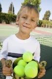 El muchacho en el campo de tenis que sostenía el trofeo llenó del retrato de las pelotas de tenis Fotos de archivo