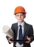 El muchacho en el casco de protección sostiene la hoja de papel y la tableta picosegundo Imagen de archivo