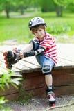 El muchacho en el casco puso pcteres de ruedas Imagenes de archivo