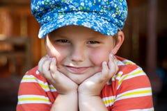 El muchacho en el casquillo azul se sienta Imagen de archivo libre de regalías