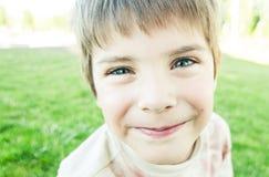 El muchacho en el parque sonríe en la cámara Foto de archivo