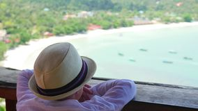 El muchacho en el sombrero que mira en la distancia el mar y las montañas del viewpoin Ver almacen de metraje de vídeo
