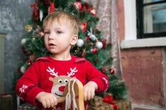 El muchacho en el suéter rojo en el caballo de madera por el Año Nuevo Fotografía de archivo