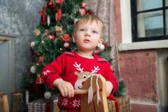 El muchacho en el suéter rojo en el caballo de madera por el Año Nuevo Imágenes de archivo libres de regalías
