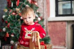 El muchacho en el suéter rojo en el caballo de madera por el Año Nuevo Fotografía de archivo libre de regalías