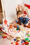 El muchacho en el suelo juega bloques varicoloured Imágenes de archivo libres de regalías
