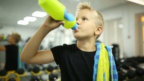 El muchacho en el gimnasio es agua potable almacen de metraje de vídeo