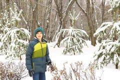 El muchacho en invierno viste caminar en parque de la ciudad de la nieve Foto de archivo libre de regalías