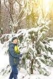 El muchacho en invierno viste caminar en parque de la ciudad de la nieve Fotos de archivo
