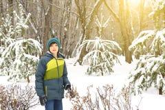 El muchacho en invierno viste caminar en parque de la ciudad de la nieve Foto de archivo