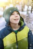 El muchacho en invierno viste caminar en parque de la ciudad de la nieve Imágenes de archivo libres de regalías