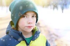 El muchacho en invierno viste caminar en parque de la ciudad de la nieve Fotografía de archivo