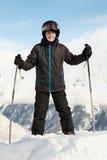 El muchacho en juego de esquí se coloca que se inclina en polos de esquí Imágenes de archivo libres de regalías