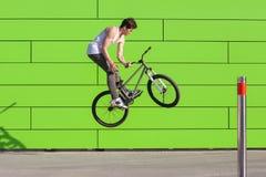 El muchacho en la bici hace que el barspin engaña en el fondo verde de la pared Fotos de archivo