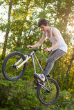 El muchacho en la bici hace que el conejito salta truco Fotografía de archivo libre de regalías