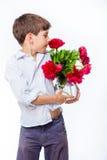 El muchacho en la camisa blanca con las peonías y el florero de cristal riegan Foto de archivo libre de regalías