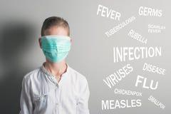 El muchacho en la máscara médica cubrió su cara al lado del nombre de enfermedades en fondo gris fotos de archivo libres de regalías