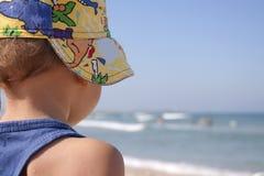 El muchacho en la playa. Foto de archivo