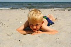 El muchacho en la playa del mar fotos de archivo
