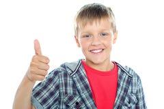 El muchacho en la ropa de moda que muestra los pulgares sube la muestra Fotos de archivo libres de regalías