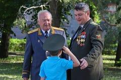 El muchacho en los mayores que saludan del casquillo en fila el día de la victoria en Stalingrad Imagenes de archivo