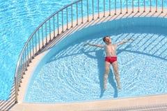 El muchacho en los troncos rojos que flotan en la piscina Imagen de archivo libre de regalías