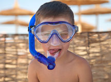 Muchacho lindo en máscara del salto en la playa Imagenes de archivo