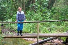 El muchacho en madera, en el puente de madera Fotografía de archivo libre de regalías