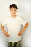 El muchacho en pantalones cortos y la camisa blanca se coloca y sonríe fotografía de archivo