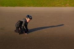 El muchacho en pcteres de ruedas se levanta después de caer Imagenes de archivo