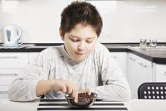 El muchacho en pijama que come el cereal muerde el primer Imagenes de archivo