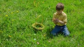 El muchacho en prado recoge los huevos de Pascua coloridos metrajes